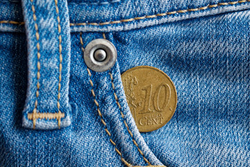 Euro coin with a denomination of ten euro cent in the pocket of vintage worn blue denim jeans