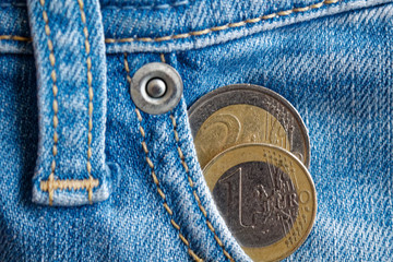 Two Euro coins with a denomination of 1 and two euro in the pocket of worn blue denim jeans