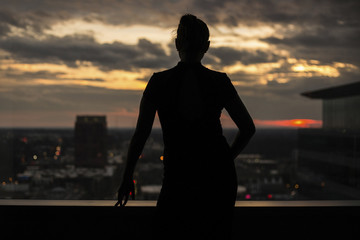 Rear view of woman standing on building terrace against city during sunset
