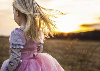 Girl walking on field against sky during sunset