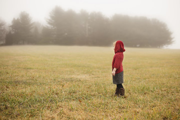 Side view of girl standing on field during foggy weather