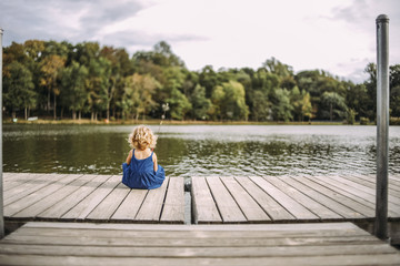 Rear view of girl fishing in lake while sitting on pier