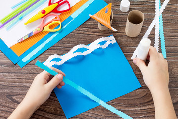 Child sticks paper boat parts, congratulations concept of Father's Day. Glue, scissors and paper on a wooden table. Children's art project craft for kids. Craft for children.