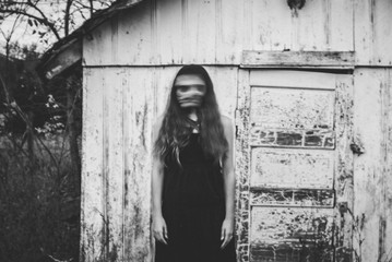 Blurred motion of woman standing against cottage during Halloween