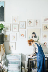 Side view of female artist working at table in studio