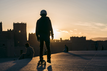 Rear view of man skateboarding against sky during sunset