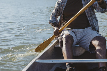 Midsection of man rowing boat on lake