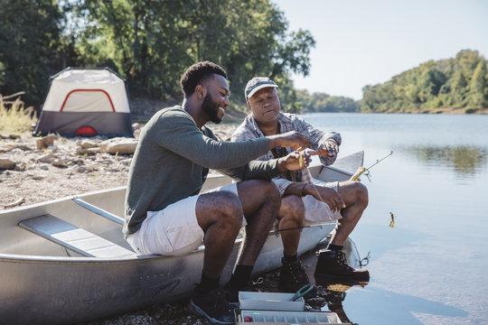 Friends adjusting fishing tackles on boat at lakeshore