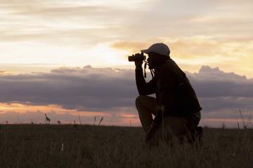 Side view of man using binoculars while kneeling on field at Serengeti National Park during sunset