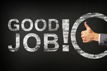 Hand of a businessman showing thumbs up for the phrase Good Job! written on a blackboard