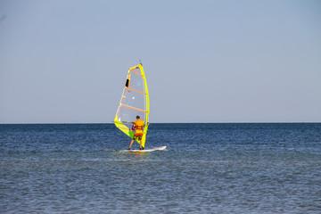 Windsurfing. Surfer exercising in calm sea or ocean.