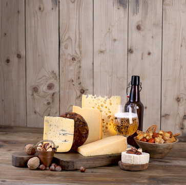 different cheese classic choice, on an old wooden board, nuts, snacks and a glass of beer and a bottle