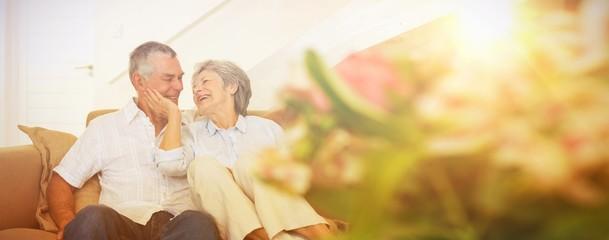 Loving senior couple sitting on sofa