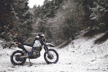 Motorcycle in a winter forest snow on the background of snowy trees. Winter extreme fun. Motorcycling in the winter. extreme fun in winter on a motorbike, enduro off road dual sport travel