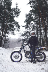 Rider man on a motorcycle Winter motocross. Skid on a snowy forest. the snow from under the wheels of a motorcycle Enduro. off road dual sport travel tour, active life style concept vertical
