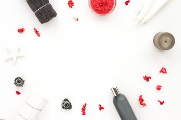 Spa composition on white background. Pink sea salt, grey candle, towel, pink flowers. Flat lat, top view