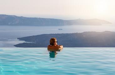 Mann genießt seinen Urlaub in einem Infinity Pool mit Sicht über das Meer