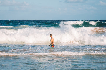 Young man swimming in huge waves on the island of Kauai, Hawaii