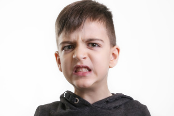 Studio portrait of preschool 5 yerars old boy on the white background - angry facial expression