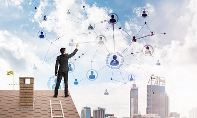 Businessman on house roof presenting networking and connection concept. Mixed media
