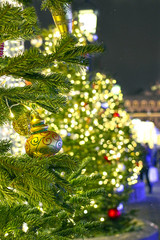 Colorful spruce decorated with yellow and red balls with lights on background