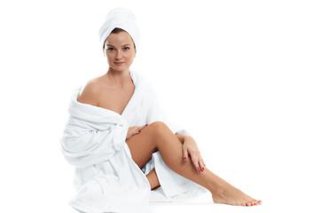 Spa. Beautiful girl in bathrobe.  Smooth female legs after depilation.
