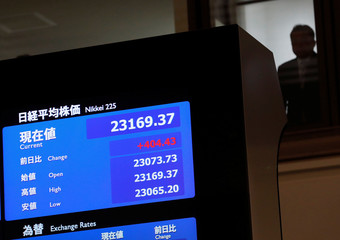 A man is seen behind an electronic board displaying the Nikkei average after the ceremony which kicks off the first day of trading in 2018 at the Tokyo Stock Exchange in Tokyo