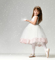 Young little girl model in the white communion  winter dress stands in gold crown with expensive gems