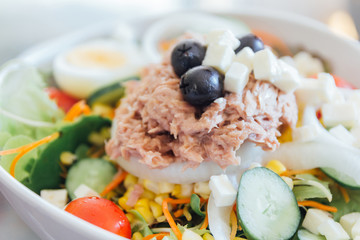 Tuna salad in a bowl with lettuce, eggs, corn, black olives, and tomatoes..Close up homemade fresh tuna salad.