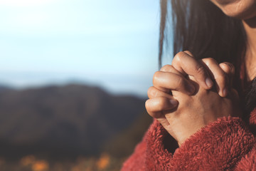Woman hands folded in prayer in beautiful nature background with sunlight in vintage color tone