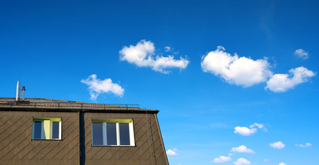 Roof of apartment building with windows on blue sky background.