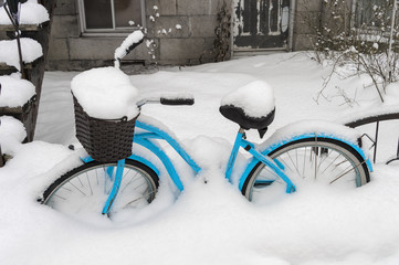 Blue bike covered in snow after snow storm in Montreal