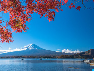 Fuji mountain with red maple and the fisherman on the boat in the lake when autumn leaf season of Japan in coming.