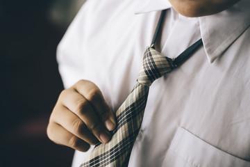 young boy holding his tie / necktie