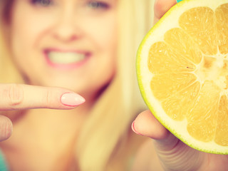 Woman pointing on grapefruit citrus fruit