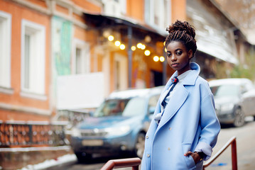 Stylish African girl in the blue coat on the street with bokeh and car in the background Wall mural
