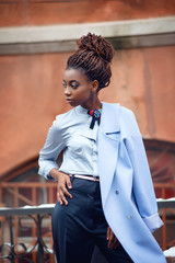 African girl with bright makeup and a blue coat stands and looks to the side on the snowy streets in style fashion