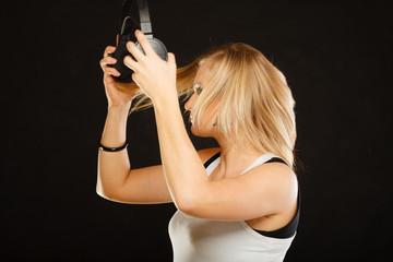 Blonde woman holding big headphones in studio