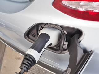 Electric Vehicle or EV car charging electric power in battery via EV charging socket and plug. Green energy concept.