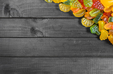 jelly and marmalade candies on a wooden background with free space for text.
