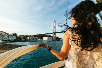 Young beautiful girl on a walk through Istanbul on a boat, bridge on a background