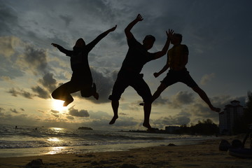 Three friends jumping to the sky