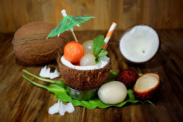 Tropical fruits: longan, rambutan and papaya ball-shaped pieces are lying in coconut. Cocktail ingredients