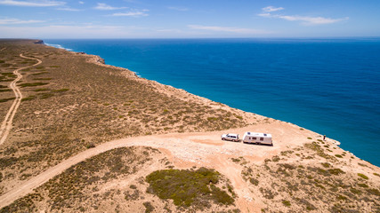 Aerial view of four wheel drive vehicle and caravan parked at The Great Australian Bight on the Edge of the Nullarbor Plain