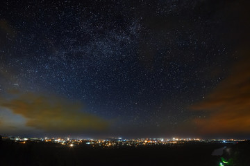 The Milky Way of the starry night sky above the city.