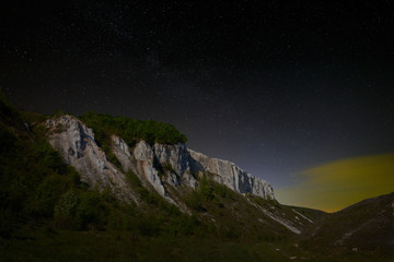 Night starry sky. View of the cliff in the moonlight.