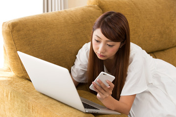 ノートパソコン・スマートフォンを持つ女性