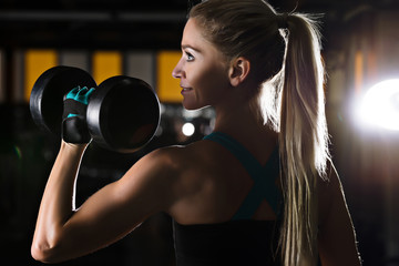 Strong muscular woman is working out with dumbbell in black gym. Hard crossfit training