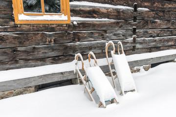 Tiefer Winter, Schlitten lehnen an einer Hüttenwand, Hüttenzauber