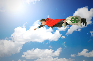 Super hero money man is flying in the sky with bag with money.